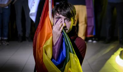 A man sits draped in a rainbow flag in a nightclub in Bucharest, Romania, Sunday, Oct. 7, 2018, after hearing of the partial voter turnout.