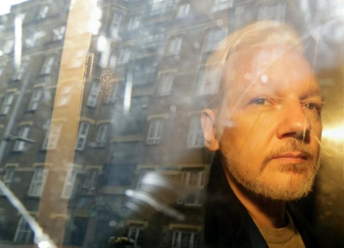 In this May 1, 2019, file photo, buildings are reflected in the window as WikiLeaks founder Julian Assange is taken from court in London