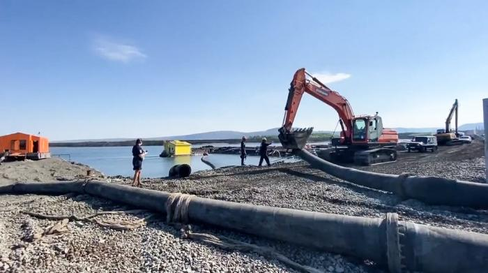 In this photo released Sunday June 28, 2020, by Novaya Gazeta, showing what the report is an excavator disassembling a pipe from a Norilsk Nickel enrichment plant with water gushing into a river which also runs into the lake near Norilsk, 2,900 kilometers (1,800 miles) northeast of Moscow, Russia