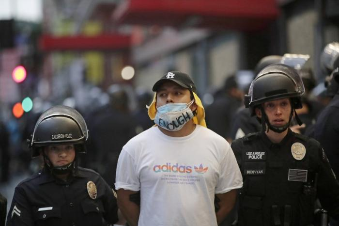 In this June 2, 2020, file photo, a demonstrator is taken into custody after the city's curfew went into effect in Los Angeles