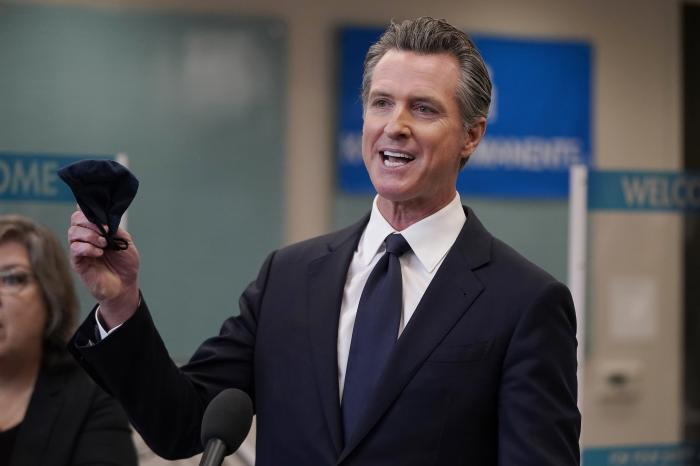 In this July 26, 2021 file photo Gov. Gavin Newsom holds a face mask while speaking at a news conference in Oakland, Calif.